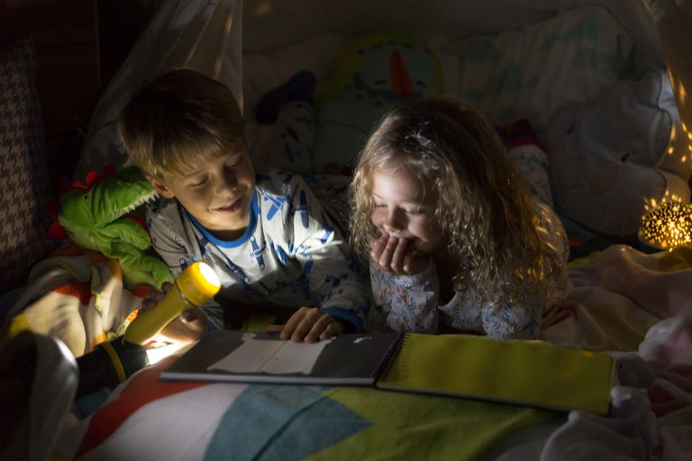 Children reading under torchlight